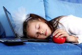 Tired girl sleeping at laptop with red apple — Stock Photo