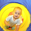 Baby playing in tube — Stock Photo