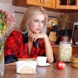 Stock Photo: Woman breakfast with apple and cup of hot drink in the kitchen