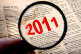 2011 text in old paper with magnifying glass — Stock Photo