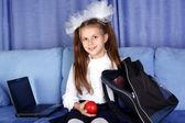 Skolflicka tjej med bärbara, ryggsäck och rött äpple i soffa — Stockfoto