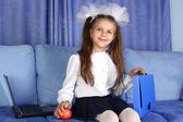 Chica colegiala con ordenador portátil, morral y rojo manzana en sofá — Foto de Stock