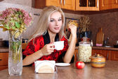 Woman breakfast with apple and cup of hot drink in the kitchen — Stock Photo