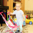 Baby playing with doll and stroller — Stock Photo