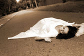 Bride laying at road — Stockfoto