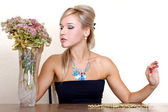 Woman looking a autumn flowers against yellow wall at table — Stock Photo