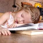 Tired little girl sleep at books — Stock Photo