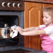 Little girl taken the food out of the kitchen oven — Stock Photo #4510561