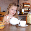 Little girl breakfast with teapot and cup of hot drink in the ki — Stockfoto
