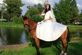 Bride horseback at brown horse — Stock Photo