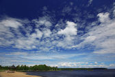 Blue cloudy sky and lake — Stock Photo
