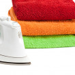 Stock Photo: Iron and stacked colorful towels.