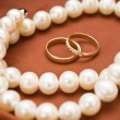 White pearls and wedding rings — Stock Photo
