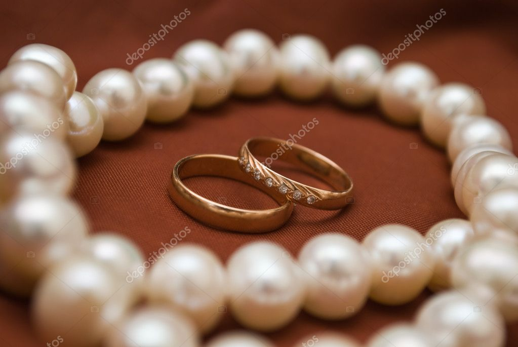 White pearls and wedding rings on the black fun — Stock Photo #4991772