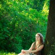 Beautyful woman sitting next tree — Stock Photo