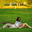 Couple laying on park lawn — Stock Photo