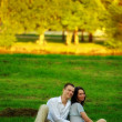 Couple sitting on park lawn — Stock Photo