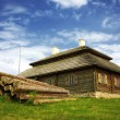 Wooden cottage on green hill - Stock Photo