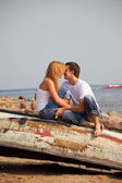 Couple sitting on old boat and kiss — Stock Photo