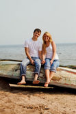 Couple on a beach sitting on old boat — Stock Photo