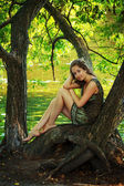 Beautiful girl sitting on a large tree — Stock Photo