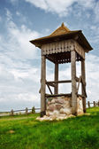 Village well on green hill — Stock Photo