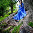 Elf princess in roots of big tree — Stock Photo