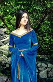 Beautiful princess standing near trees — Stock Photo
