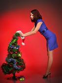 Beautiful girl decorating christmas tree — Stock Photo