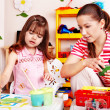 Child with teacher draw paints in play room. — Stock Photo #3932623