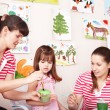 Child painting with teacher in preschool. — Stock Photo #3932630