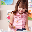 Child preschooler painting in classroom. - Stock Photo