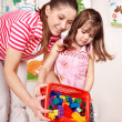 Child with wood block and construction set in play room. — Stock Photo #3932640