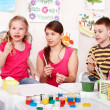 Foto Stock: Child with teacher draw paints in play room.