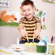 Child with brush draw red sun in play room. — Stock Photo