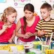 Children with teacher painting in play room. — Stock Photo