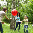 Stock Photo: Outdoor happy family plaing ball .