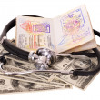 Stock Photo: Medical still life with stethoscope, money and passport.