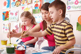 Children painting with teacher in art class. — Stok fotoğraf