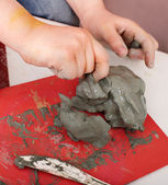 Child moulding from clay in play room. — Stock Photo