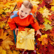 Child in autumn orange leaves and gift box. — Stock Photo #3955390