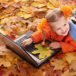 Royalty-Free Stock Photo: Child in autumn orange leaves with laptop.