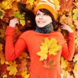Young woman in autumn orange leaves. - Stock fotografie
