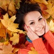 Girl in autumn orange hat on leaf group. — Stock Photo #3955423