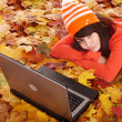 Girl in autumn orange leaves with laptop.Fall sale. — Stockfoto