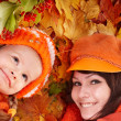 图库照片: Happy family with child on autumn orange leaves.
