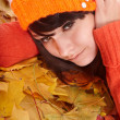 Girl in orange hat on leaves with sad face. — Stock Photo #3955431