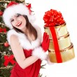 Christmas girl in santa hat and fir tree with stack gift box. — Stock fotografie