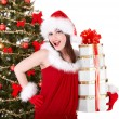 Christmas girl in santa hat and fir tree with stack gift box. — Stock Photo #3955479