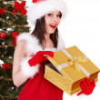 Christmas girl in santa hat and fir tree with gold gift box. — Stock Photo #3955481